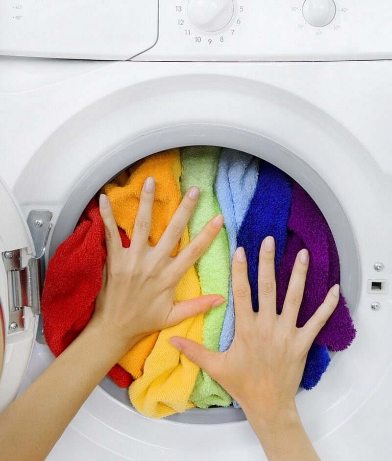 woman-loading-clothes-colorful-laundry-in-the-washing-machine