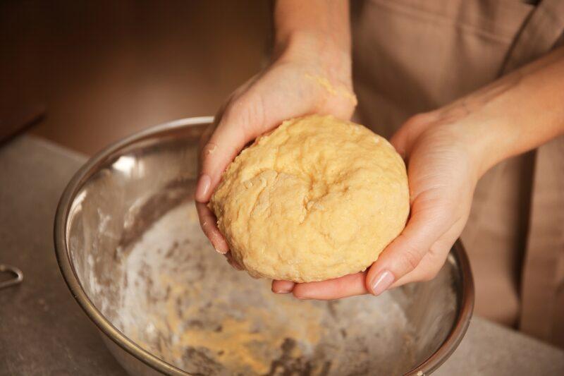 young-woman-making-dough-in-kitchen-closeup