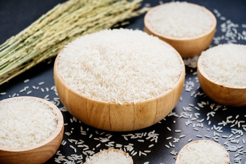 raw-jasmine-rice-in-wooden-bowl-and-spoon-with-grain-and-seed