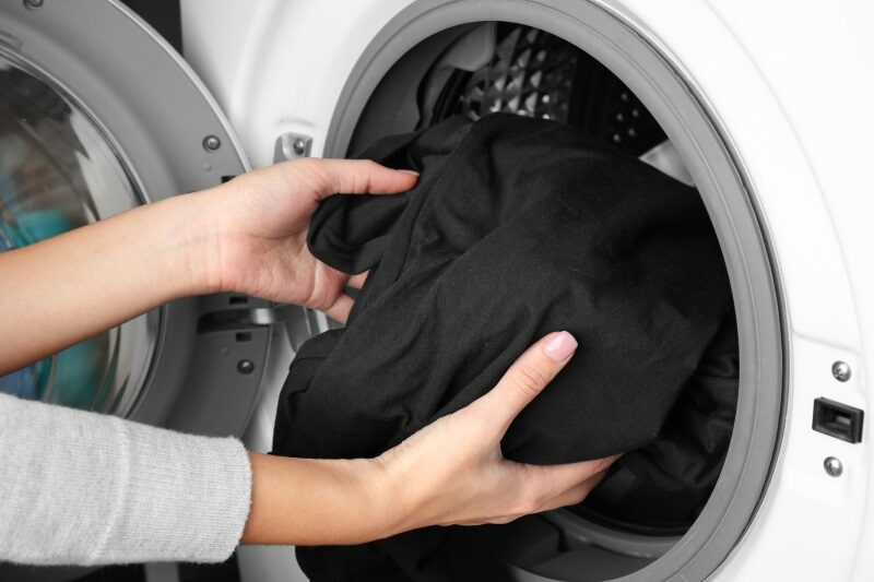 female-hands-getting-out-clean-clothes-from-washing-machine