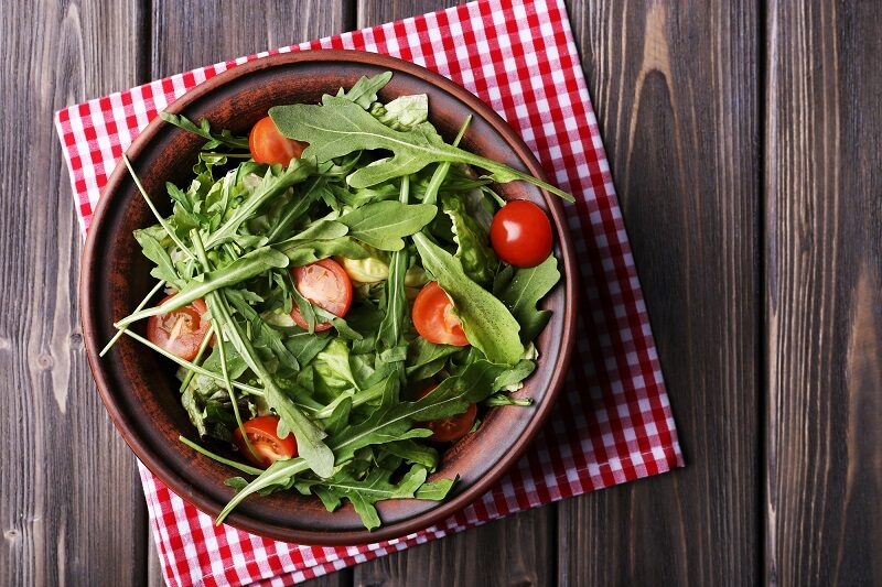 salad-with-arugula-and-cherry-tomatoes-on-wooden-table